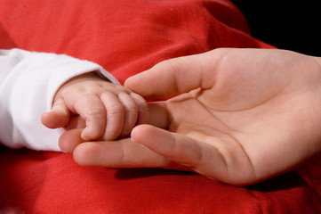 Close-up of babys hand holding sisters hand
