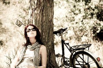 Beautiful girl sitting near bike Photo in retro style.