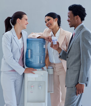 Business people speaking next to a water cooler