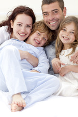 Portrait of young family lying in bed