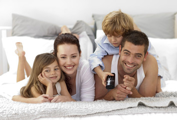 Family lying in bed watching television