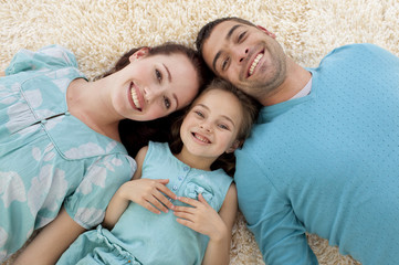 High angle of parents and daughter on floor with heads together