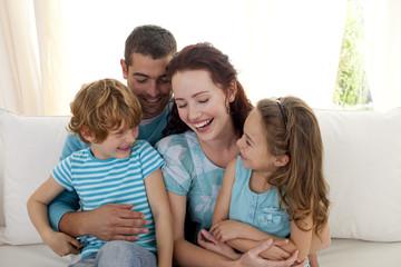 Family sitting on sofa having fun