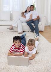 Children using a laptop on floor in living-room