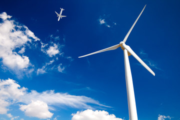 wind turbine on blue sky and airplane