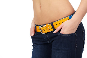 Closeup photo of a slim woman's abdomen and jeans with measuring