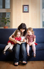 Mother reading a book to her little daughters
