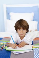 Portrait of little boy drawing in bed