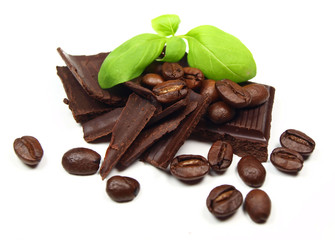 Chocolate pieces and slices with coffee beans and basil leaves