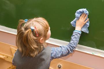 The girl wipes a blackboard