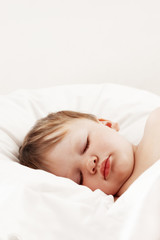 cute baby sleeping in white bed