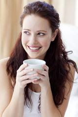 Beautiful woman drinking a cup of coffee in bed