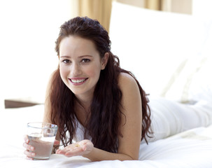 Woman in bed taking pills with water