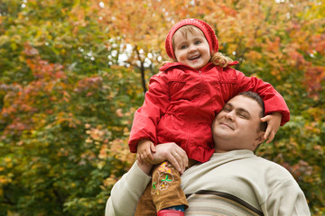 little girl sits on shoulder at man In park in autumn