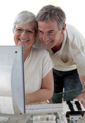 Senior couple using a computer at home