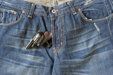 Blue-jeans with a colt bulging out of the zipper