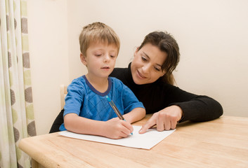 Mother helping her son with writing.