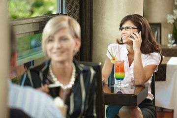 Businesswoman talking on mobile in cafe