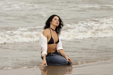 Ragazza sexy con jeans al mare in una giornata di pioggia
