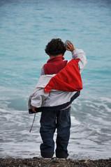 enfant seul de dos à la plage en hiver jetant des pierres