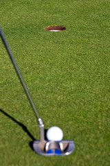 Golfer lining up a short putt with focus on the hole
