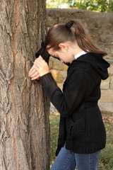 Portrait girl of the teenager in a jacket , jeans near a tree.