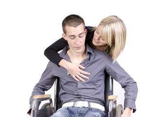 jeune femme enlacant homme dans chaise roulante