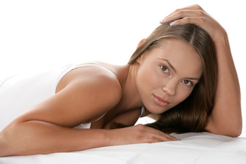 Portrait of young woman lying on stomach looking at camera