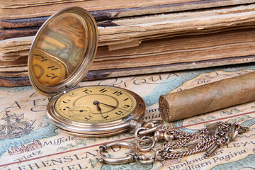Golden pocket watch with cigar and books
