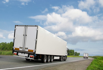 white trucks on  country highway under blue sky, rear view