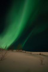 Aurora polaris over a mountain slope.