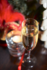 Sparkling wine and candle in blurred festive background