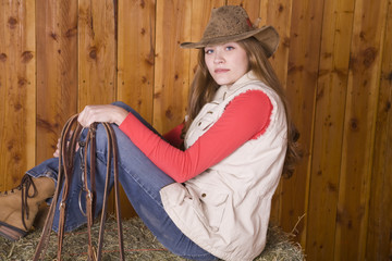 Woman sitting on hay with bridle