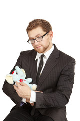 Businessman sitting and looking at the plush toy