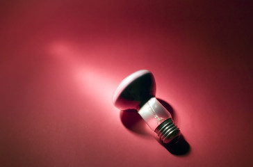Electric bulb on red background