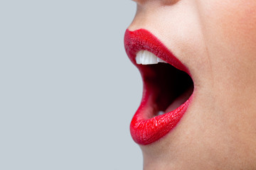 Womans mouth wide open with red lipstick.