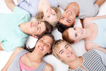 Friends lying on floor with heads together