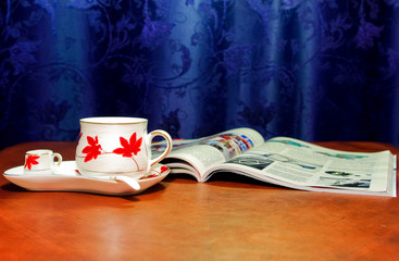 Magazine and cup on table