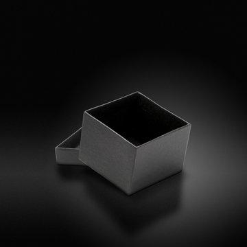 Boîte grise sur fond luxueux noir - paquet cadeau de luxe