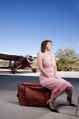 Attractive red-head infront of a classic plane