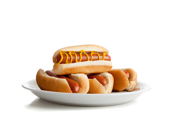 Stacked hot dogs with mustard and buns on white