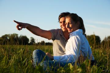 Paar auf Wiese bei Sonnenuntergang