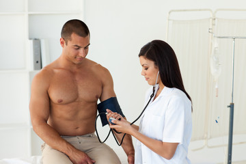 Confident female doctor checking the blood pressure of a patient
