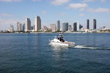 A San Diego skyline and a patrol boat.