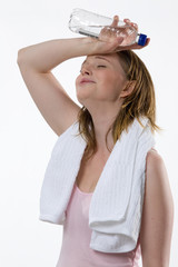Frau nach dem Fitnesstraining trinkt Mineralwasser aus Flasche