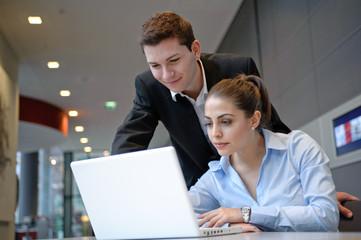 mitarbeiter besprechen sich an laptop in büro