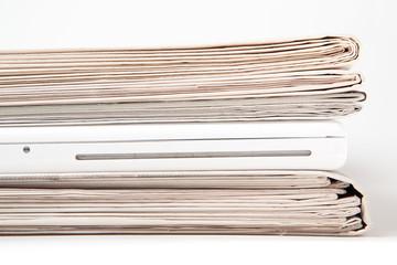 Zeitungsstapel mit Laptop dazwischen