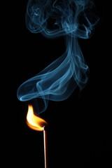 Rauchendes Zündholz vor schwarzem Hintergrund