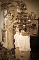 Vintage photo of Teen girl decorating Christmas tree