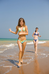 Attractive girls running along the seashore